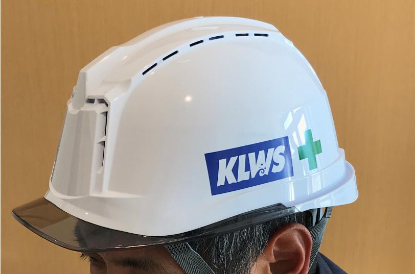 クリーンなイメージの白地に、左サイド面にはKLWSのロゴと安全(ミドリ十字)マーク(写真上)、バック面には個人ナンバー(写真下)が入る。