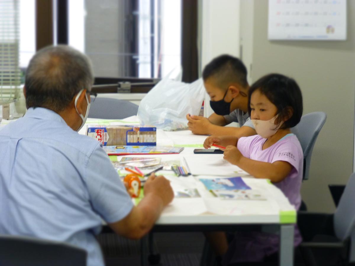 託児室で、お孫さんのような子供たちにお絵かきを教える、オーナー会菅生会長